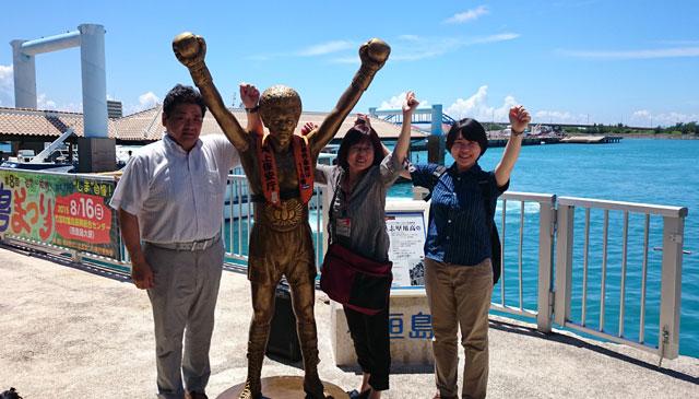 石垣島の離島ターミナルにて、ゴールドの具志堅用高さん像と。「eフレンズ」を広めるぞ〜!あ、いちばん左が私です。